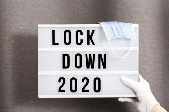 Hands in white gloves hold Light box with message lockdown 2020 and Surgical protective mask. Word of the Year 2020 is lockdown.