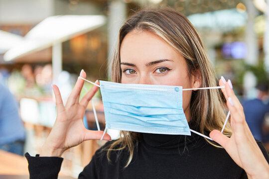 Frau zeigt das Maske richtig aufsetzen mit beiden Händen