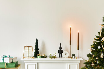 Christmas composition on the white chimney at the living room interior with beautiful decoration....