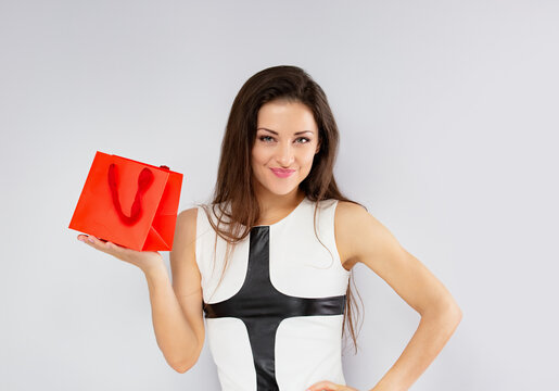Excited surprising woman in white dress looking happy and holding gift red package with smiling on blue background. Happy holidays.