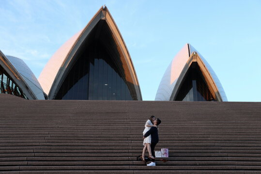 A couple embraces on the steps of the Sydney Opera House in Sydney
