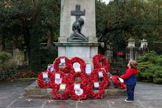 Toddler Alexander Johnson looks at a poppy placed at the Fulham War Memorial
