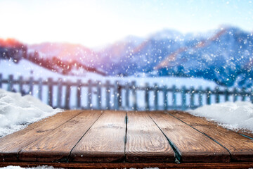 Wooden table in the snow against the backdrop of a mountain landscape at sunset