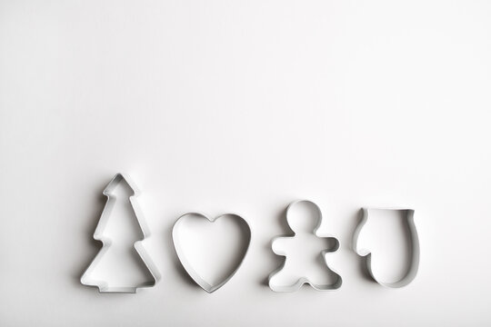 Christmas minimal white background. cookie cutters tree, heart, mitten, gingerbread man.