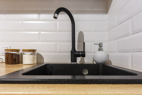 black water tap sink with faucet and soap dispenser in expensive loft kitchen