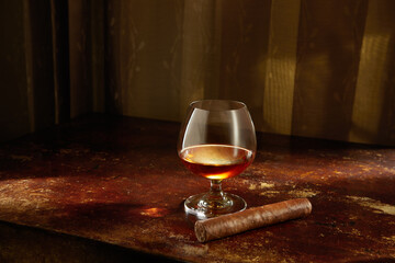 Closed up view of glass of cognac with cigar aside on color back