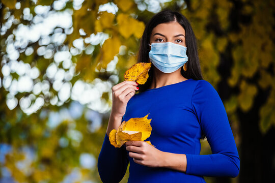 Beautiful young woman wearing a  medical mask and with yellow maple leaf in hand covering her face.
