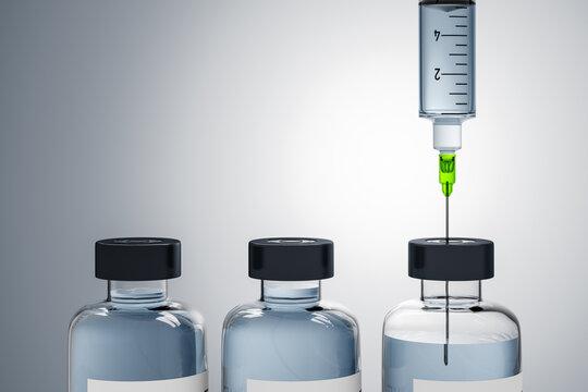 A syringe and three bottles of medicine