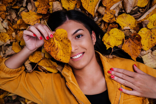 Beautiful young woman laying and smiling on the oak and maple leaves in the park.