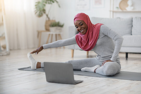 Black muslim woman in hijab exercising in front of laptop at home