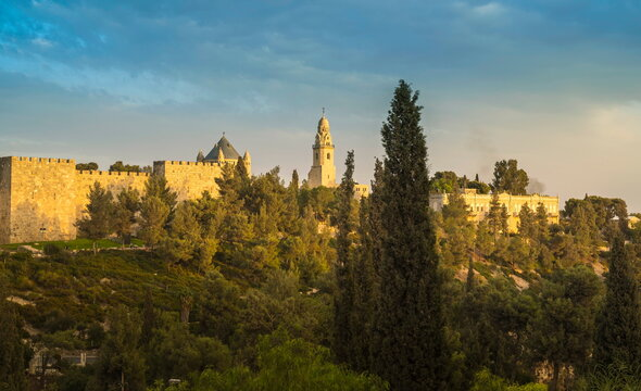 Sunlit view of the Old City wall of Jerusalem, and the Dormition Abbey on Mount Zion, with its lead-covered basilica and a bell tower - also a traditional site of King David's tomb
