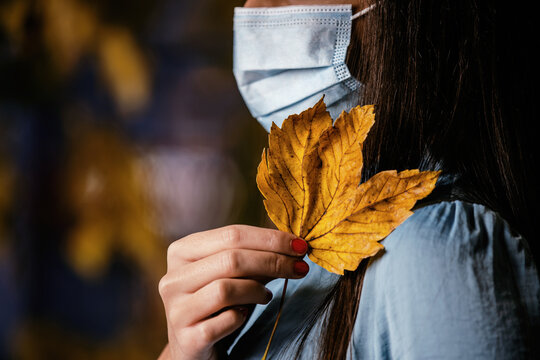 Beautiful youg woman wearing a medical mask in royal blue and holding yellow maple leaf in hand.