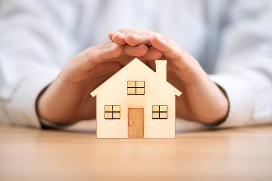Wooden toy house protected by hands. Home insurance concept