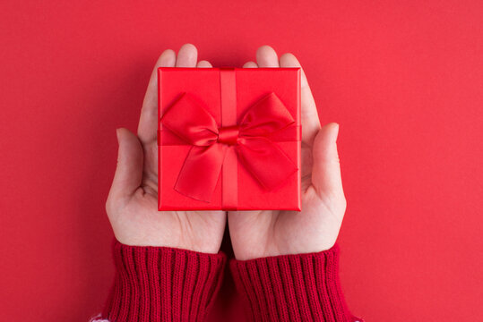 Giving present to friend concept. Top above overhead close up first person view photo of woman holding small box with little bow isolated bright color background