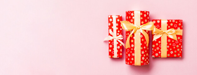 Wall Mural - Gift box with gold bow for Christmas or New Year day on pink background, top view