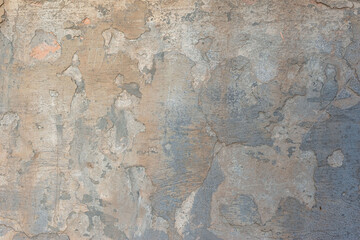 texture of brown old plaster on the street wall of the house. Warm shades