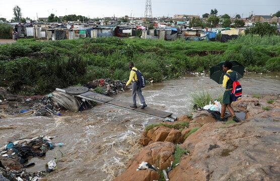 School children cross a makeshift bridge after heavy rains in Thembisa