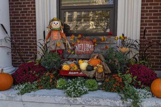 Autumn season pumpkin patch décor with a scarecrow is put up to welcome locals and tourists alike in Bar Harbor, Maine. The town relies heavily on tourism and has a quaint, small town feel.