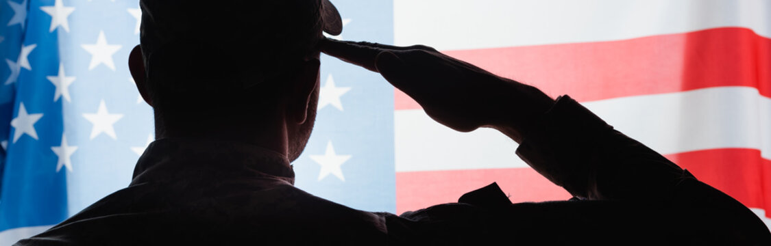 back view of patriotic military man in uniform giving salute near american flag on background, banner