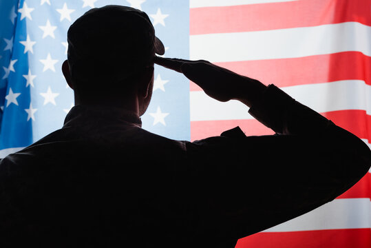 back view of patriotic military man in uniform and cap giving salute near american flag