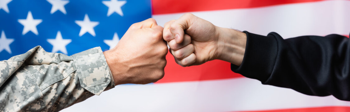 cropped view of soldier fist bumping with civilian man near american flag on blurred background, banner