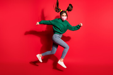 Profile side photo of pretty brown haired tails girl wear green sweater jeans mask run jump copyspace isolated on red color background Wall mural