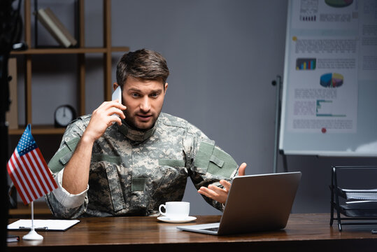 patriotic military man in uniform talking on smartphone near american flag, cup and laptop
