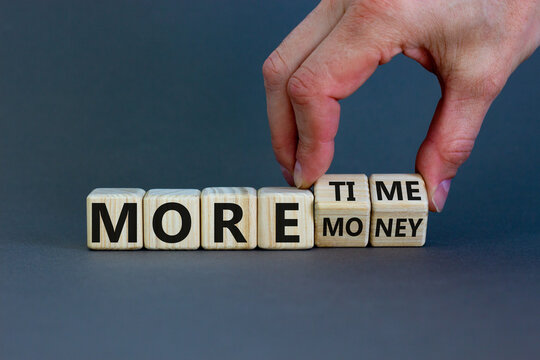 More time or more money. Male hand flips wooden cubes and changes the inscription 'more money' to 'more time' or vice versa. Beautiful grey background, copy space. Concept.