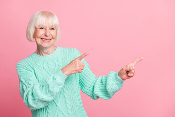 Photo portrait of female pensioner bob hairstyle pointing with fingers on blank space recommending...