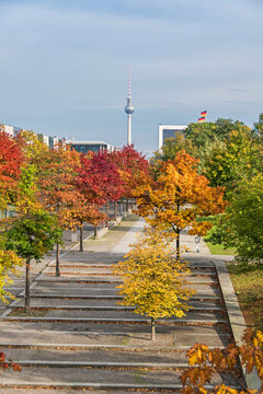 Paul Loebe Allee lined with autumn coloured trees and the television tower in Berlin, Germany