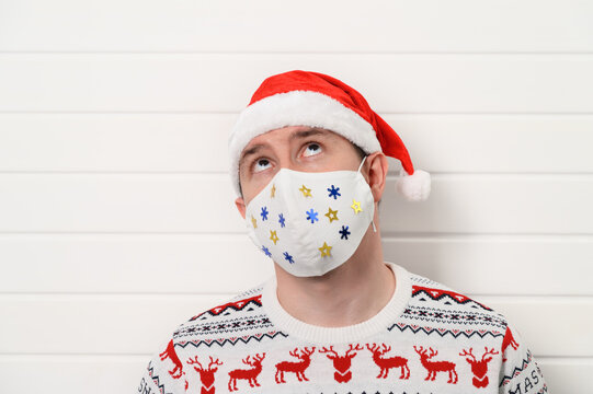 Close up portrait of adult person wearing white medical fabric mask, Santa hat and sweater, isolated over white background. Stay home. Christmas coronavirus concept. Copy space