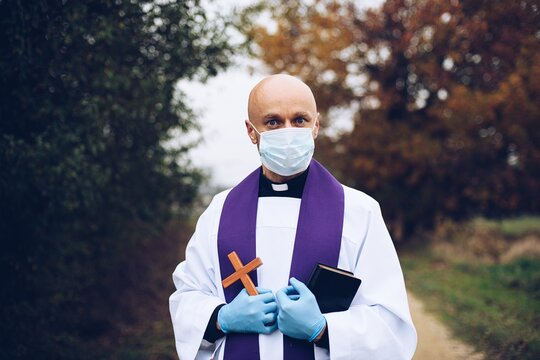 Man priest in a protective mask and protective gloves during a pastoral visit.