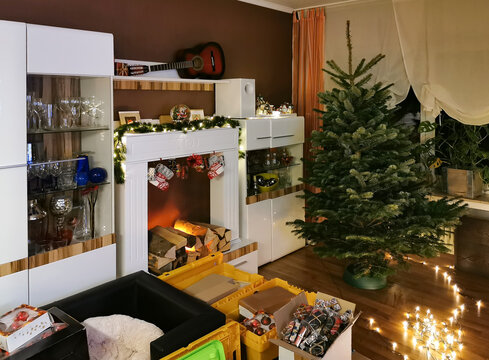 A real Nordmann fir tree is decorated for the Christmas tree. In the living room there are many boxes with jewelry. The light chain is still on the floor.