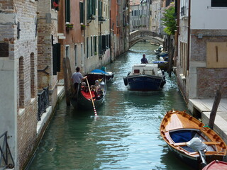 A gondola gives way to a motorboat in a narrow Venetian canal. A bridge over the canal and boats moored to its banks.
