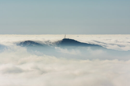 Mountain with antennas on its summit that protrudes through the clouds, creating an island in a sea of clouds.