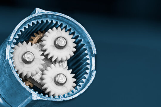 White planet gears inside a ring cogwheel of epicyclic gear train on blue background. Close-up of plastic and metallic cog wheels in disassembled gearbox of electric screw gun. Mechanical engineering.