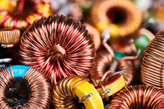 Toroidal electronic inductors on heap in electrotechnical background. Closeup of beautiful induction coils with copper wire winding on magnetic ferrite core. Colored electrical engineering components.