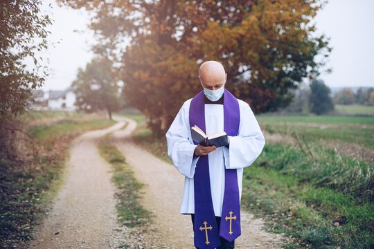 Young priest reads the holly bible in the field