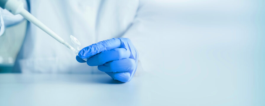 Hands of a scientist who works with pipette and a test tube. Research technician in the genetic laboratory. medical and research banner