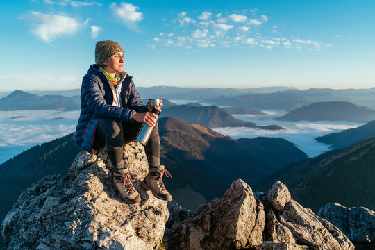 Young hiker woman sitting on the mountain summit cliff, drinking tea from a thermos flask and enjoying mountains valley covered with clouds view. Successful summit climbing concept image.