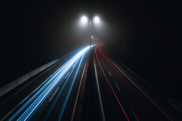 Horizontal photo of cars light trails on a curved highway at night with street lamps over the road. Motion blur image -  city road with traffic headlight motion (top view) in foggy and misty weather.