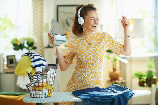 woman ironing on ironing board while listening to the music