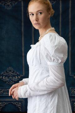 A Regency woman wearing a white muslin dress standing alone in a room