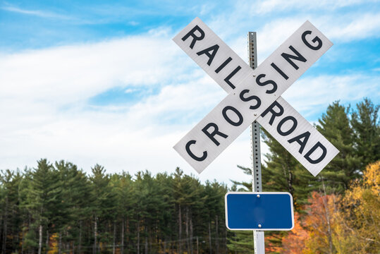 Railroad crossing sign with trees in background on aclear autumn day. Copy space.