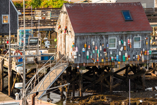 Wooden fishing hut wiht hanging colourful buoys at the end of pier in a fishing harbour at sunset. Kittery, ME, USA.