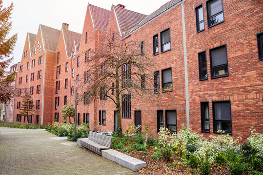 Row of modern brick residential buildings along a a pedestrian pathway in a housing development in winter