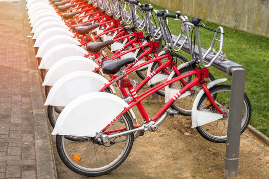 Row of colourful bikes in a bicycle sharing system docking station in apublic park in winter