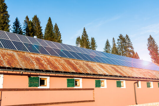 Solar panels for electricity generation over the rusty tin roof of a barn in the European Alps on a sunny autumn day. Lens flare.