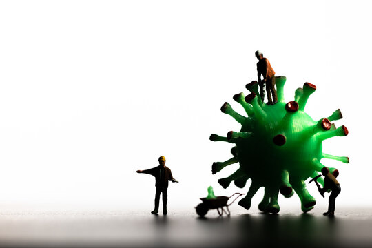 Silhouettes of Miniature workers take a sample from a viral model, on a white background close-up. Taking an analysis For the covid-19 test.  Macro illustration of the virus.