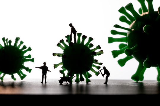 Silhouettes of Miniature workers take a sample from a viral model, on a white background close-up. Sample collection for creating a vaccine. . Macro illustration of the virus.